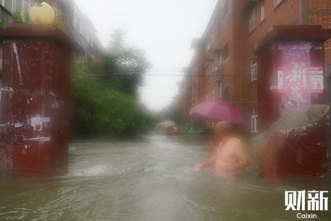 7月22日,河南省新乡市卫辉市城郊乡,受灾群众在齐胸高的积水里向外转移,两条鱼跃入记者镜头。7月21日20时至22日16时,新乡市北中部出现大暴雨、特大暴雨,截至22日15时,受灾人口增至77万余人。图/财新记者 陈亮