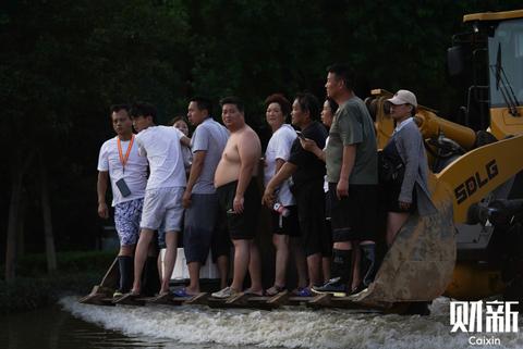 7月25日下午,河南省新乡市新中大道北与中原东路路口,受灾群众靠铲车转移到安全地带。截至24日,新乡市暴雨已造成全市11个县区116个乡镇受灾,受灾人口171万余人,约占全市人口的1/4。图/财新记者 丁刚